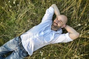 Lachender Mann liegt im Gras