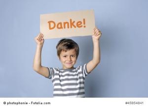 Kind sagt Danke mit einem Schild